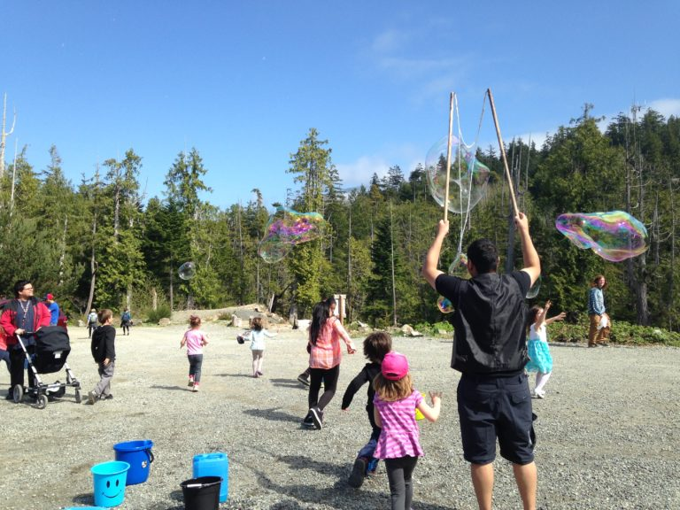 NSG Project - Clayoquot Sound. A man making large bubbles on a beach with kids running around.