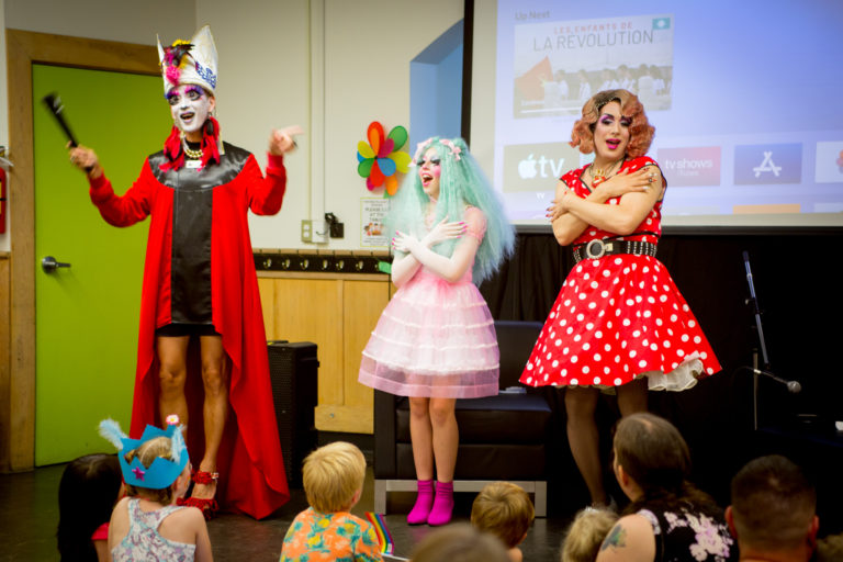 NSG Project - Kids n Queens. Three drag queens telling stories to a room of toddlers and children.