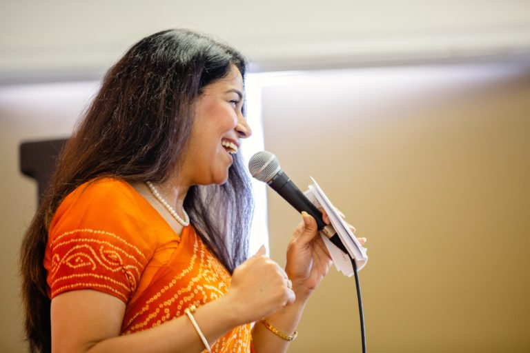 NSG Project in Surrey - Taranga. An East Indian woman in a bright orange sari speaking into a microphone.