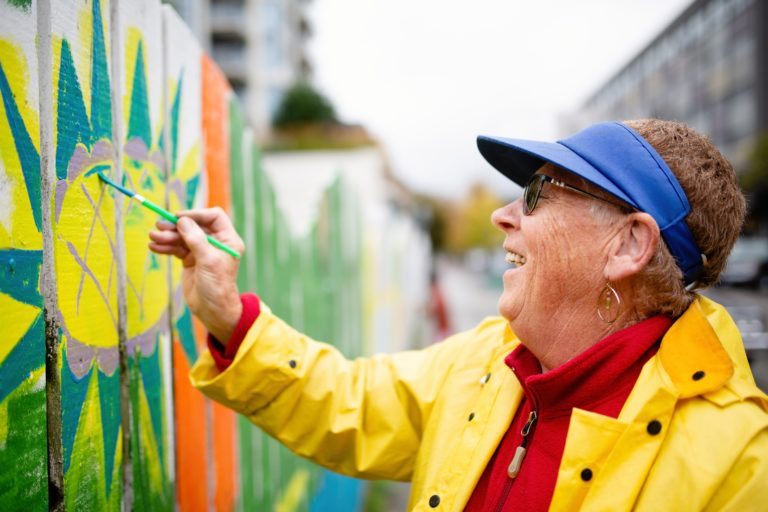 NSG Project in New West - Fence Painting. A middle-aged woman in a bright yellow rainjacket smiling as she paints a flower on a fence.