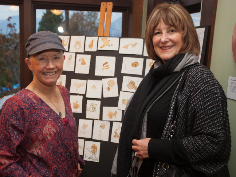 NSG Project in Victoria. Two women stand in front of a board of art.